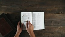 a person holding a magnifying glass over an open Bible