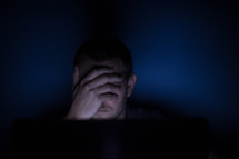 a man covering his eyes looking at a computer screen at night