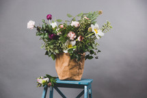 a flower arrangement on a blue ladder