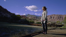 a young woman standing outdoors by a dried up pond