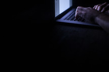 a man typing on a laptop at night