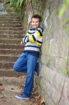 Young boy standing and posing against a old stone wall