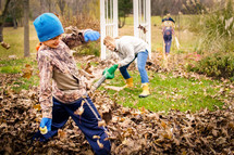 kids playing in fall leaves