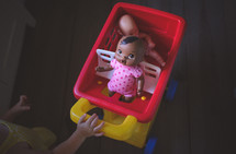 toddler pushing a babydoll in a toy shopping cart