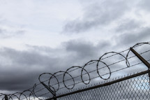 barbed wire at the top of a chain link fence under gray skies
