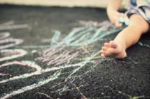 toddler playing with sidewalk chalk