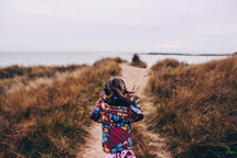 a child in a coat running towards a shore