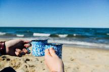 toasting coffee mugs on a beach