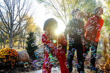 children playing with bubbles in fall