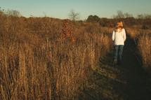 a teenager walking through a field