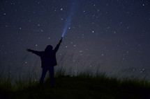 silhouette of a boy shining a flashlight into a starry night sky