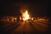 people sitting around a beach bonfire