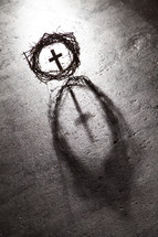 Silhouette of crown of thorns with cross in the center.