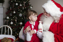 a toddler with cookies and milk sitting on Santa's lap