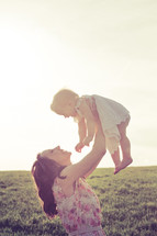 Mother holding daughter in the air in a sunny field.