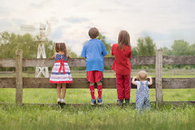 family in patriotic colors looking over a fence