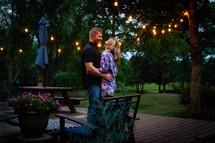a couple standing on a backyard deck hugging