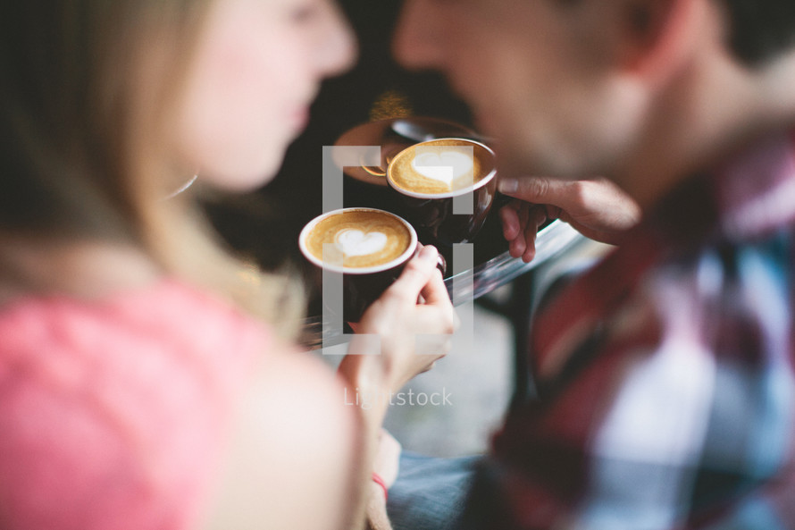 Couple drinking coffee with heart shaped foam