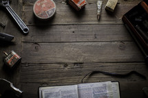 an open Bible surrounded by tools