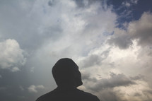 silhouette of a man looking up at the sky