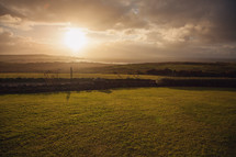 sun setting over rolling green hills