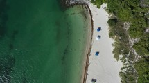 Aerial drone top-down view of beach shoreline, trees, lighthouse, tourist and water
