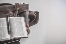messenger bag, open Bible, and journal