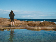 girl standing on a rocky shore in Nelson Bay