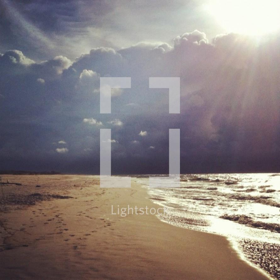 sunburst and sunlight over tide washing onto a beach