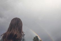 girl looking up at a rainbow in the sky