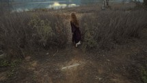 woman walking towards a shore through grasslands