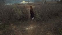 woman walking towards a shore through grasslands