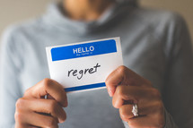 woman holding a name tag with the word regret