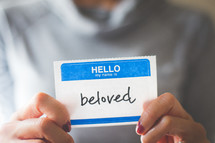 woman holding a name tag with the word beloved