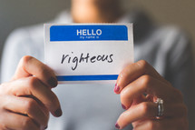 woman holding a name tag with the word righteous