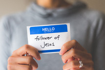 woman holding a name tag with the words follower of Jesus