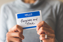 woman holding a name tag with the word forgiven and free