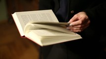 a woman turning the pages of a book