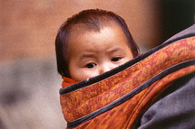 Infant Chinese child carried in a pouch on mother's back