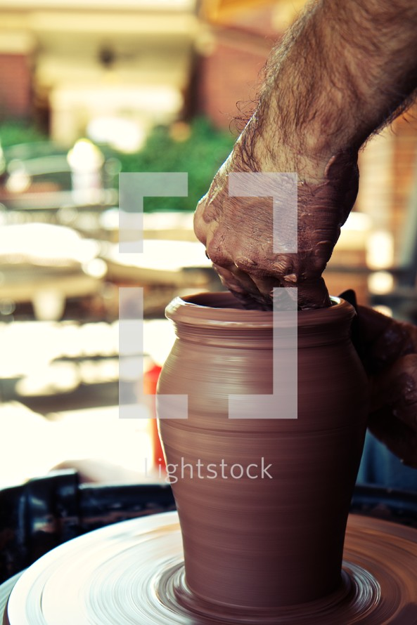 A potter puts the finishing touches on his clay pot