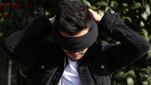a man putting on a blindfold