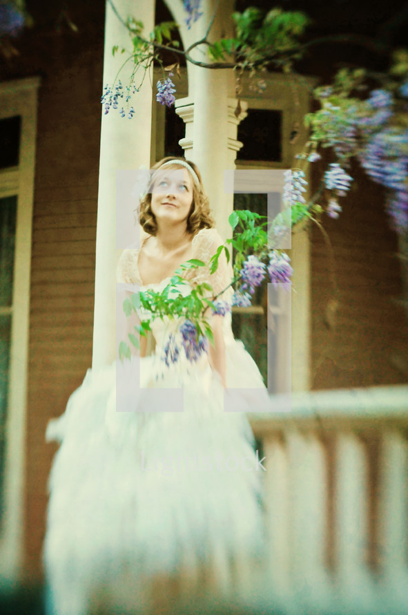 Bride sitting on front porch rail
