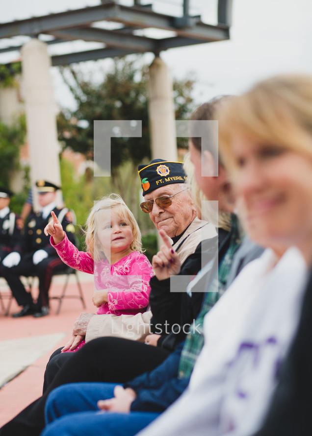 A Veteran holding his granddaughter in his lap