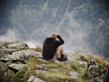 man sitting on the edge of a mountain scratching his head and enjoying the view