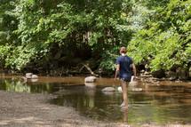a child exploring a creek