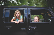 sisters looking out of Jeep windows