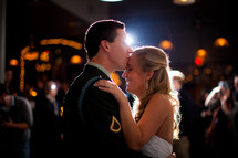military groom kissing his bride on the forehead