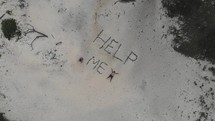 Help Me written in sand on a beach