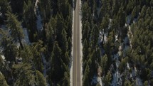 aerial view over a winer forest and road with snow