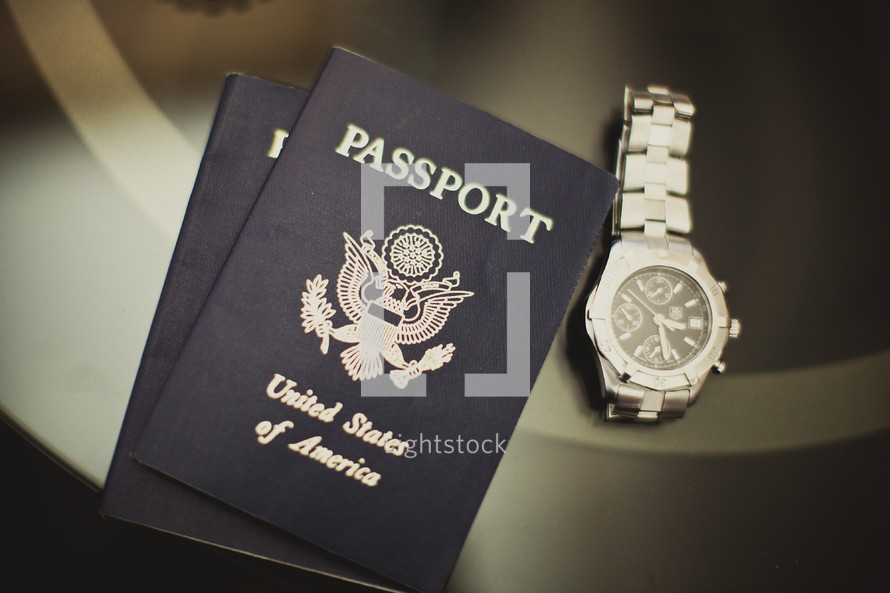 Two U.S. passports and a silver watch sitting on a table